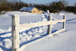 fence with house in the background and snow everywhere