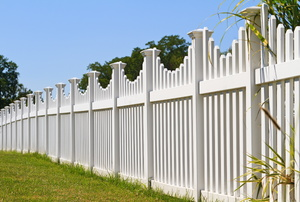 White picket fence in a yard.