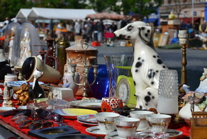 A flea market with a table full of goods for sale.