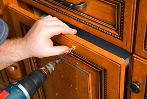 Drilling a hole to apply new pulls and fronts to old cabinets.