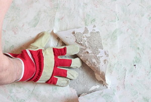 gloved hand peeling back wallpaper