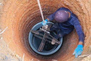person in deep hole for water