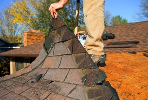Removing a damaged portion of roof shingles.