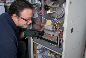 A repairman working on a furnace.