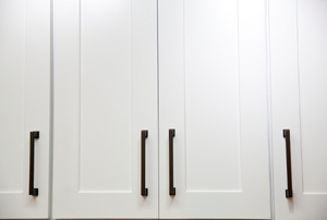 Pristine white cabinets with dark metal handles.