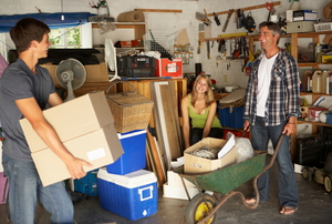 A family of three organizing a garage.
