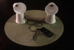 A set of speakers made from cups and earbuds.