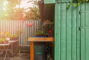 A green potting shed with gardening tools hanging around it.