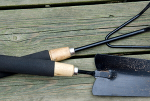 A hand cultivator and hand trowel used for gardening.
