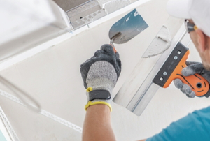 man holding drywall tools