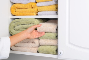 A linen closet with folded towels.
