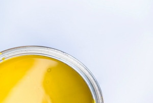An off center, close-up shot of a can of yellow enamel paint.