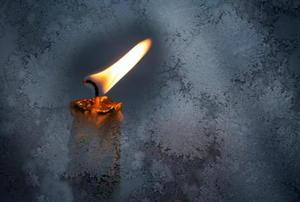 A flame burns against a dark background.