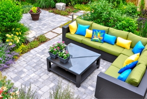 a stone patio with couches, plants and a table