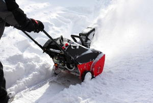 A snow blower being pushed to clear a path.