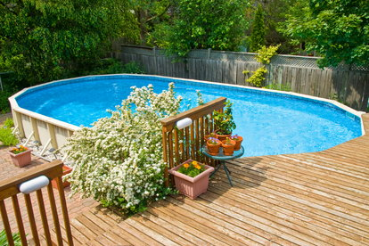 An Above Ground Pool With A Deck Next To It In Backyard