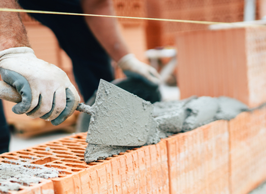 hands laying large bricks with mortar and trowel