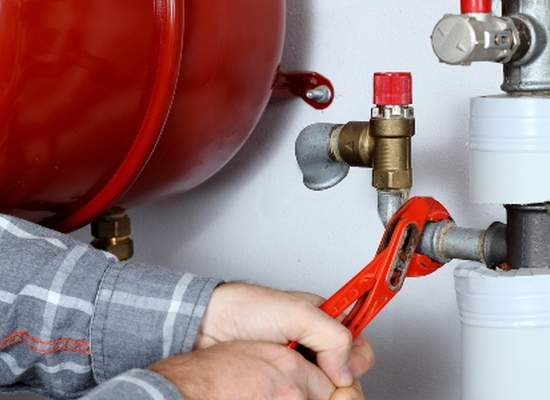 hands using wrench to fix pipes for heating system