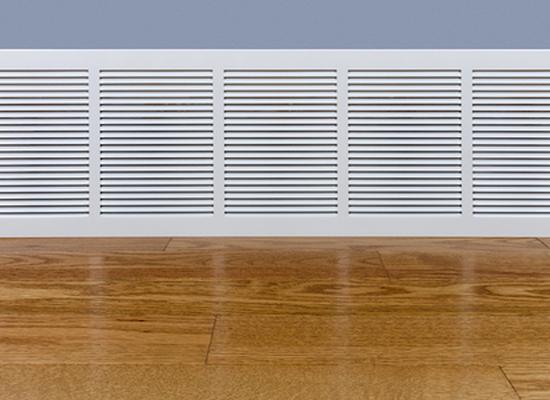 air return intake vent at base of wall by wood floor