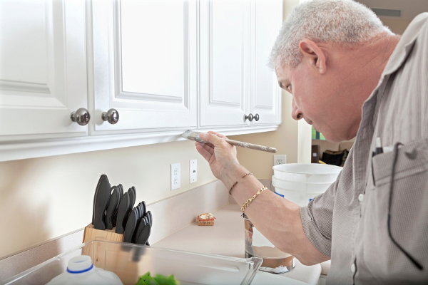 A painter working on white cabinets in a kitchen.