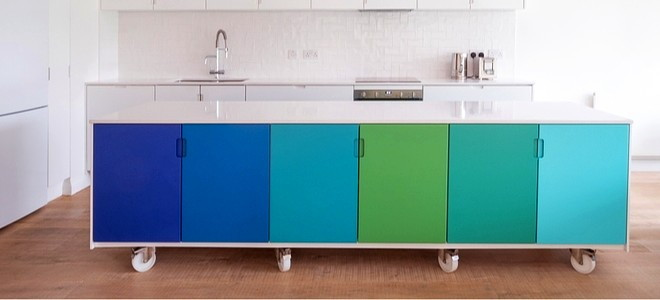a row of cabinets on wheels with different blue and green colored doors