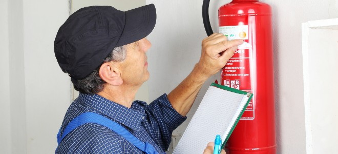 man checking the expiration date on a fire extinguisher