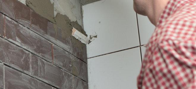 A Man Installing Flat Bricks Onto An Interior Wall.