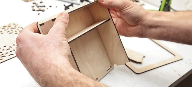 hands assembling small shadow box