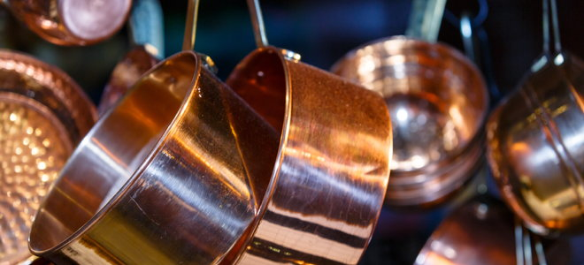 copper pots and pans hanging from a ceiling shelf