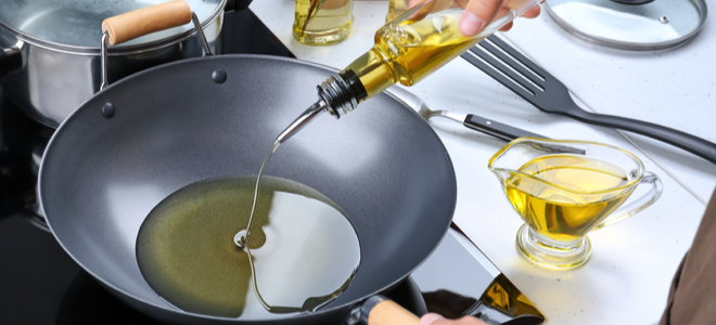 pour oil into a curved frying pan