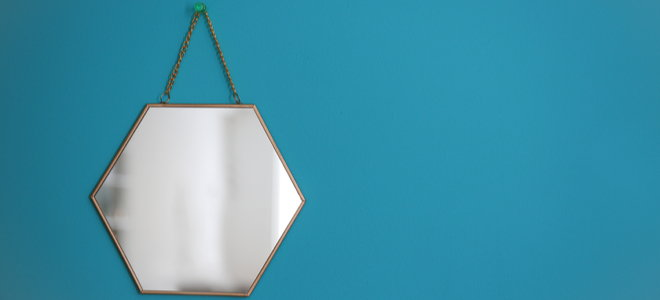 hexagonal mirror hanging on a blue wall