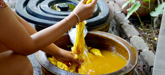hands twisting fabric in natural yellow dye