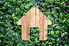 A wood outline of a house against an ivy backdrop.