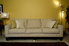 a tan sofa against a yellow wall with lamps on both sides of it.