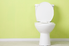 toilet sitting against a yellow wall