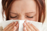 A woman overcome by allergies.