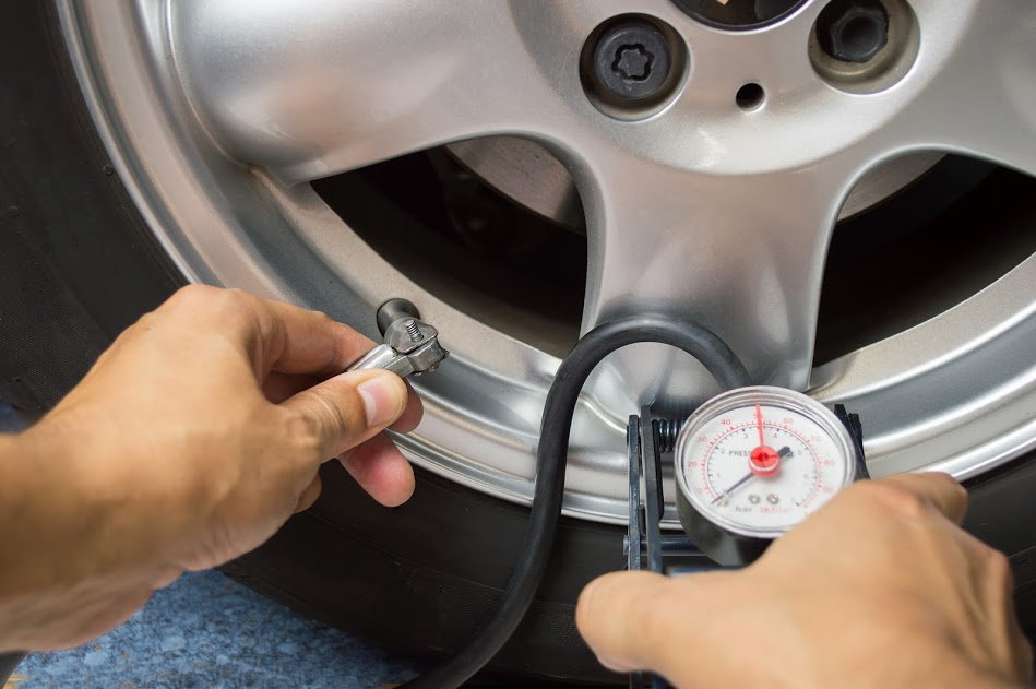 Кто-то проверяет давление воздуха в автомобильных шинах.