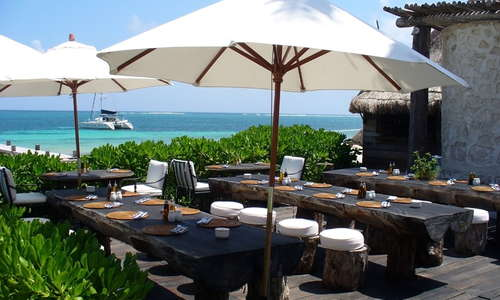 Outside tables at El Chiringuito Beachside Grill offering a variety of fresh seafood, chicken and grilled favorites cooked over native Zapote and Mesquite.