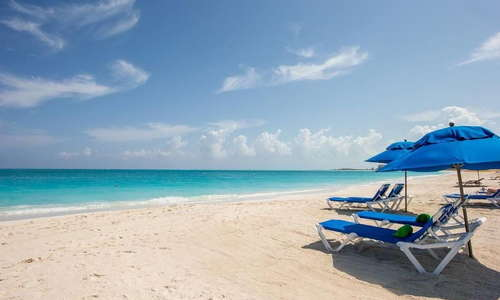 Designated beach spot on Grace Bay Beach with chaise lounges, umbrellas, stand-up paddle boards, kayaks, beach floats, and full-time beach attendant.