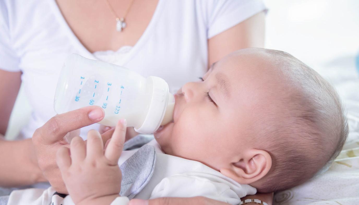 momi feeding baby a bottle of formula