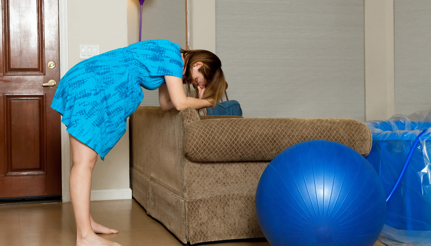 woman leaning over couch during labor