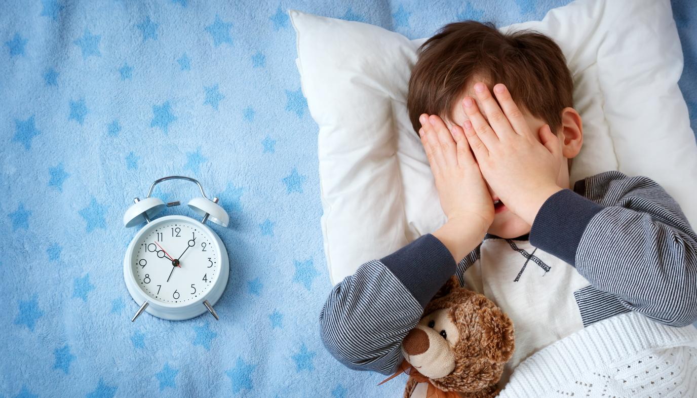 boy sleeping next to alarm clock