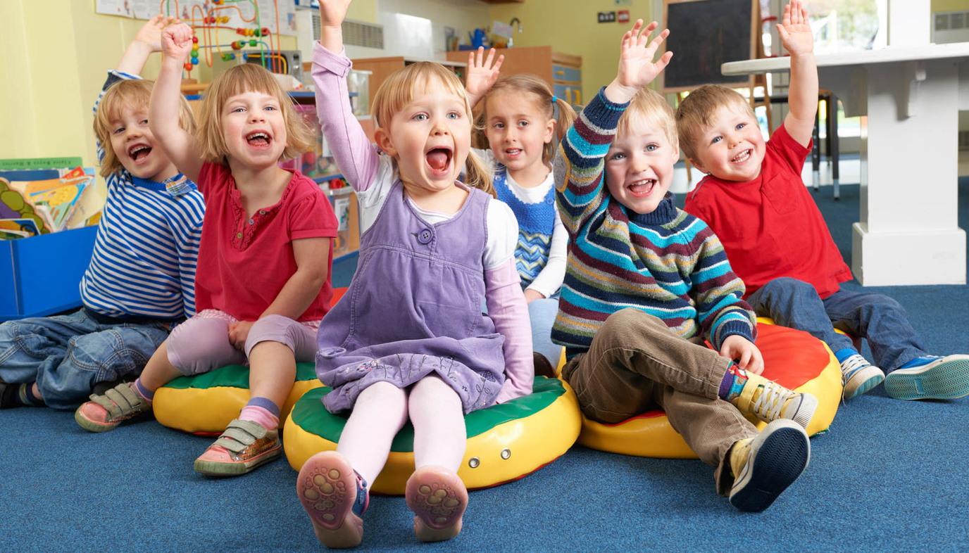 happy children in kindergarten raising their hands