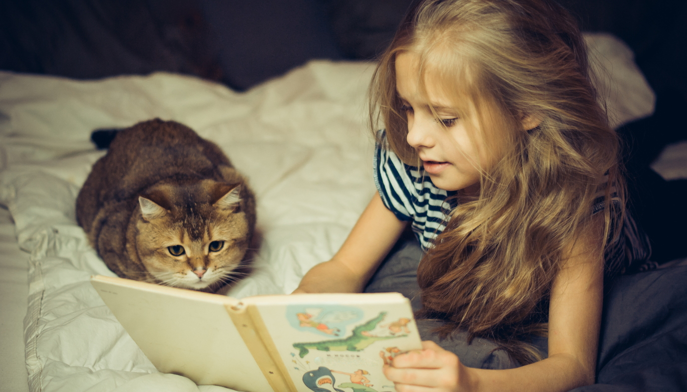 girl reading to cat