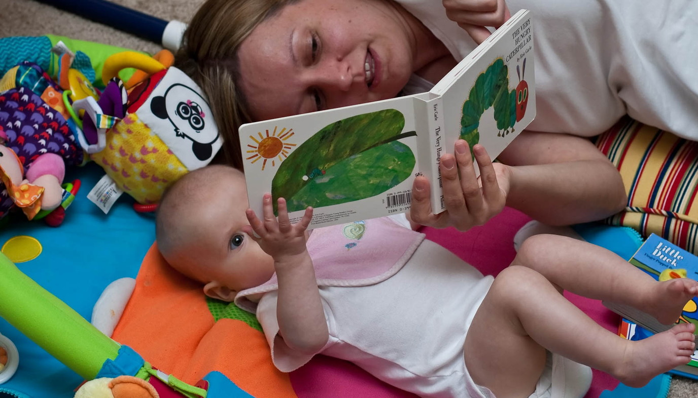 mom reading a board book to her baby