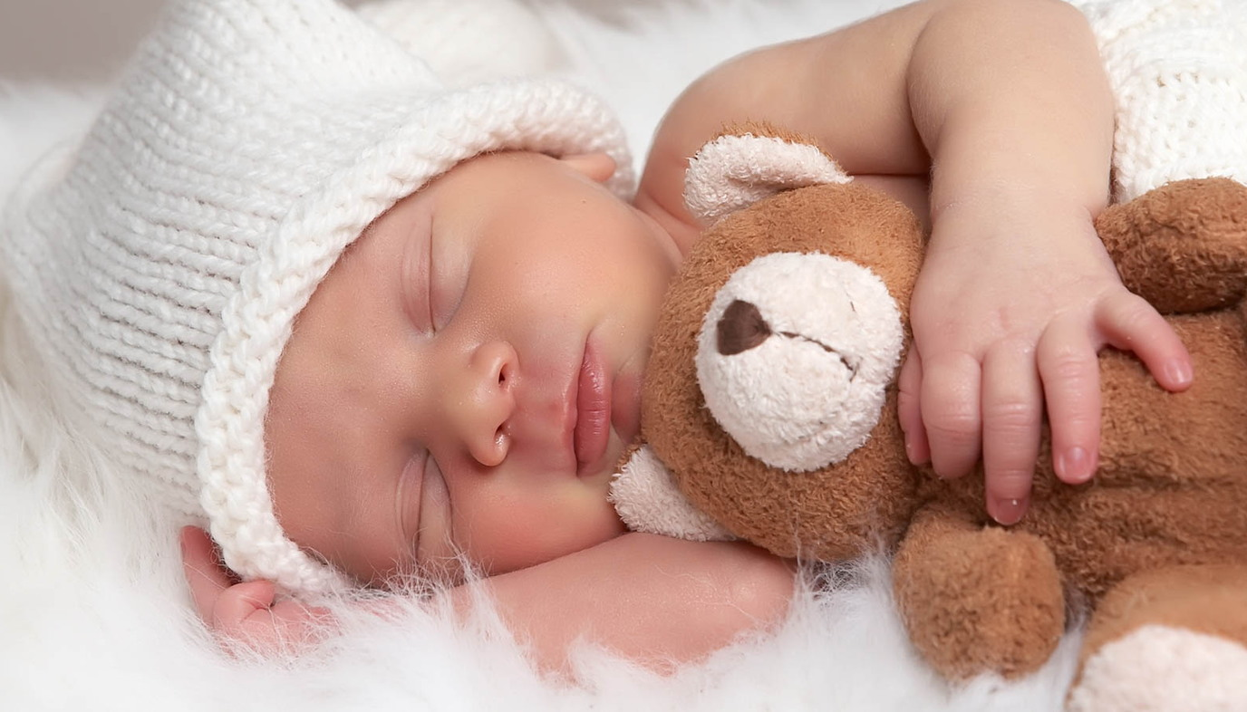 infant sleeping with a teddy bear