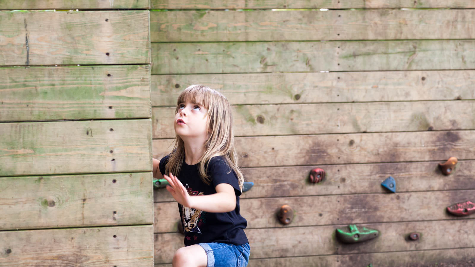 girl rock climbing up wall
