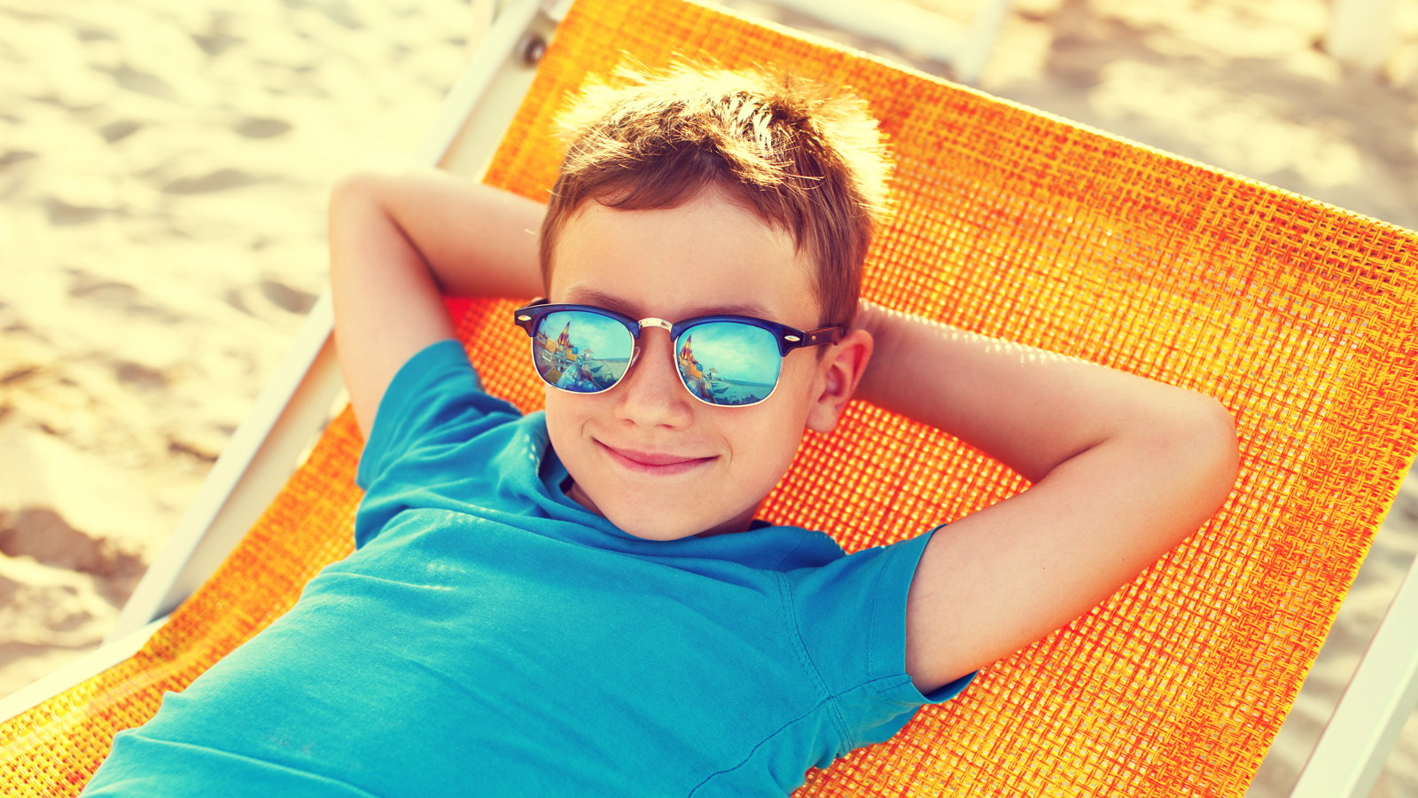 boy wearing sunglasses relaxing on the beach