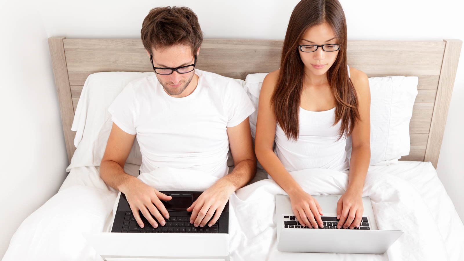 couple using laptops in bed