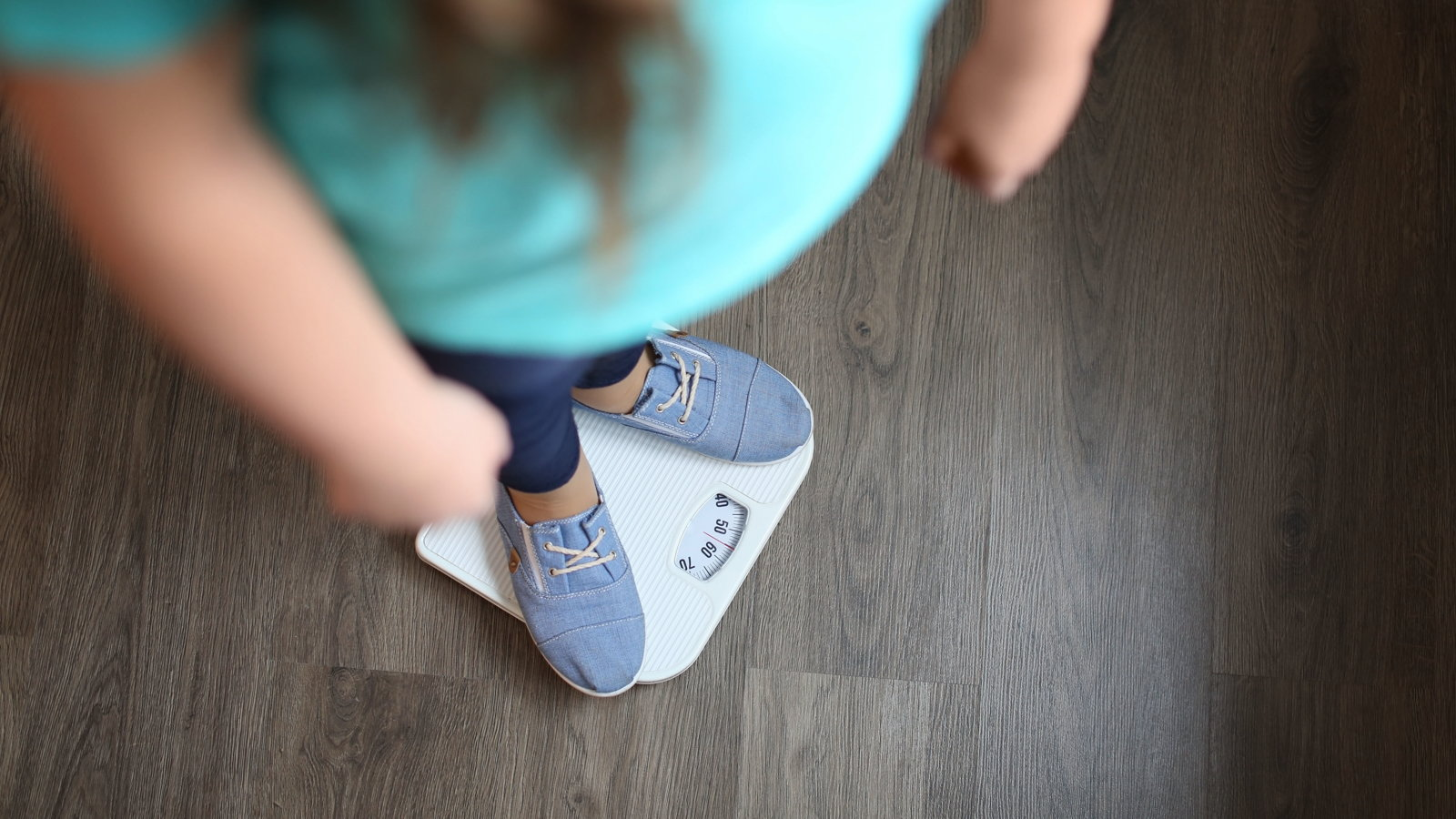 overweight girl stepping on scale